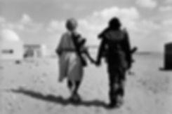 Front Polisario. Bire Enzaran. Maroc. Photographies de Jacques Bravo. deux soldats se tenant par la main avec une arme à l'épaule