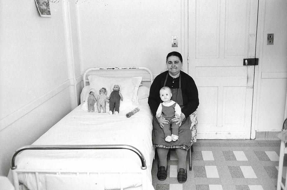L'hôpital de province, le théatre de l'oubli. Photographies de Jacques Bravo. Une femme assise pres de son lit avec une poupée sur ses genoux