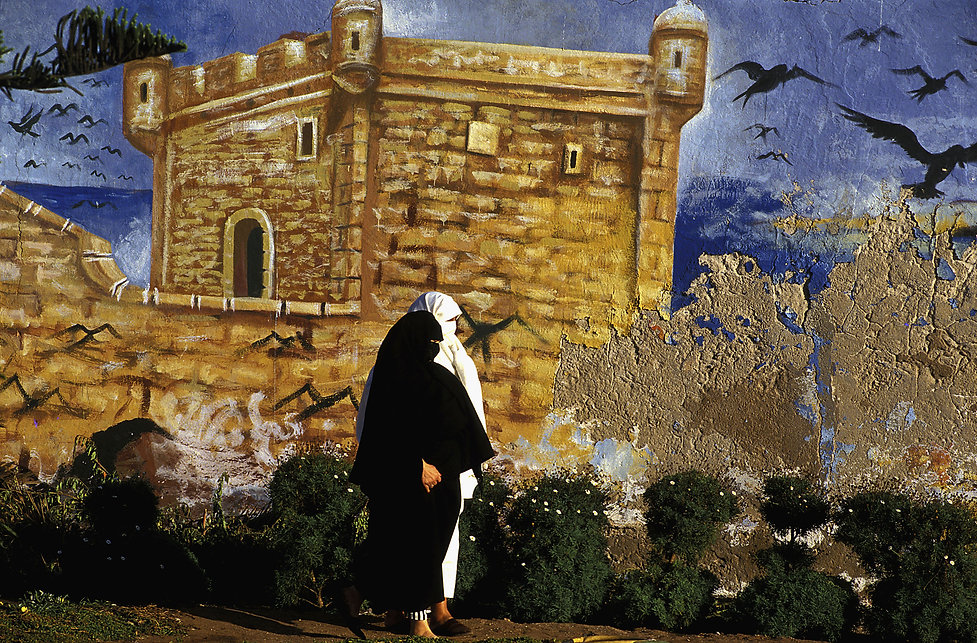 deux femmes passant devant une peinture murale à Essaouira au Maroc