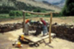 Deux enfants actionnent la manivelle d'un puits pour tirer l'eau dans la vallée des Ait Bouguemez. Photographie de Jacques Bravo