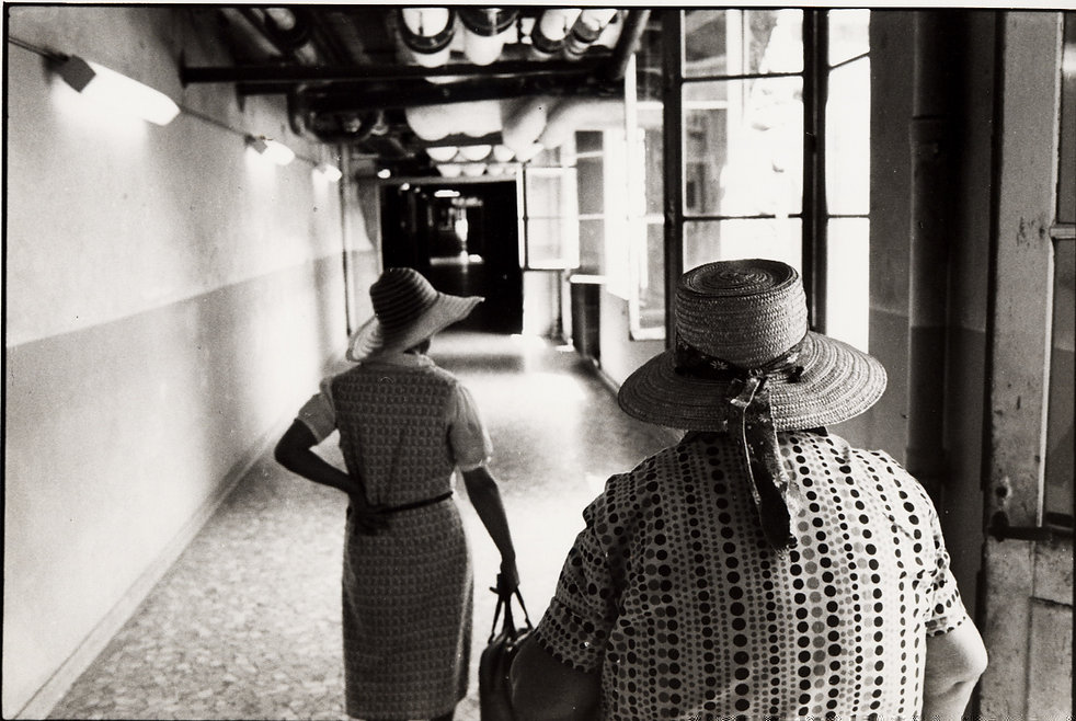 L'hôpital de province, le théatre de l'oubli. Photographies de Jacques Bravo. deux femmes avec chapeau de paille dans un couloir