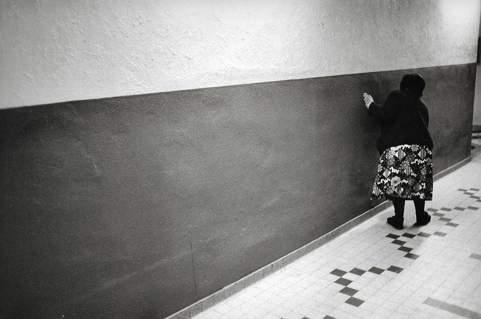 L'hôpital de province, le théatre de l'oubli. Photographies de Jacques Bravo. Une femme s'aide d'un mur pour marcher