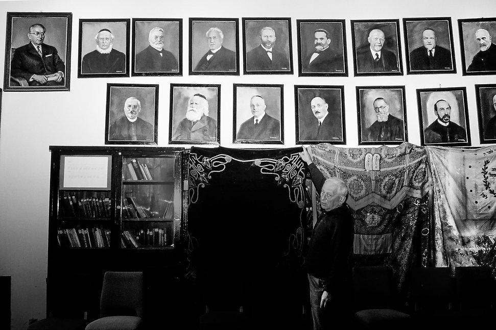Monsieur Remete,conservateur de la bibliothèque juive de Budapest avec une galerie de ses prédécesseurs. Photographie de Jacques Bravo