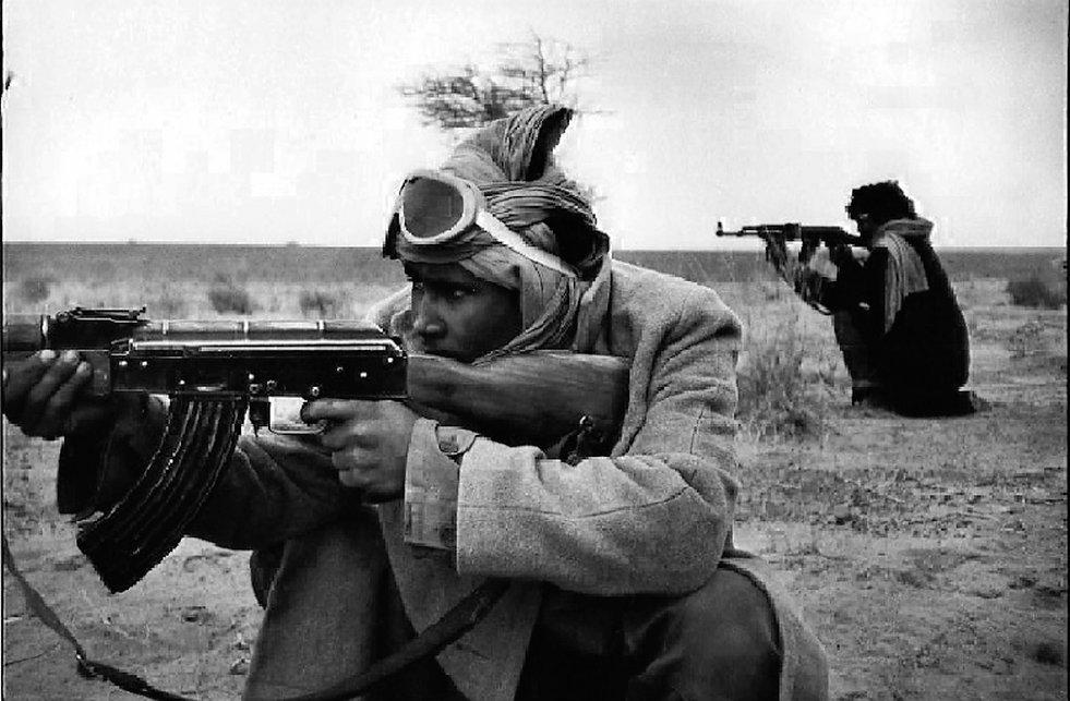Front Polisario. Amgala. Maroc. Photographies de Jacques Bravo. Soldats tirant dans le désert avec une kalachnikov