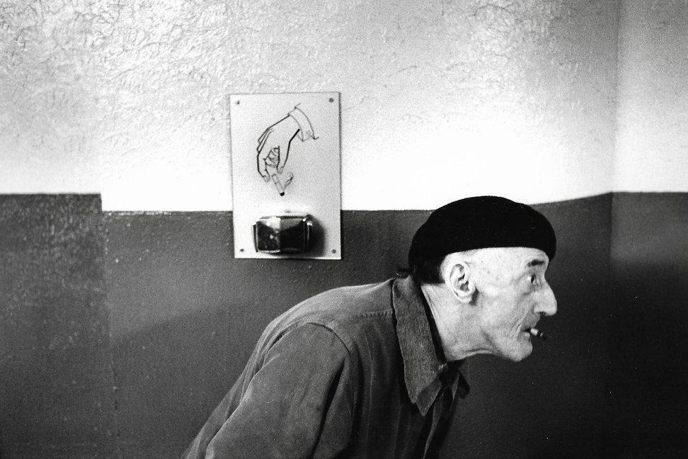 L'hôpital de province, le théatre de l'oubli. Photographies de Jacques Bravo. un homme courbé avec une cigarette