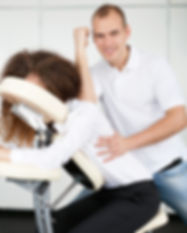Woman getting a seated shoulder massage.