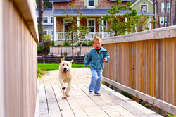 boy and dog on olivia beach boardwalk_crop