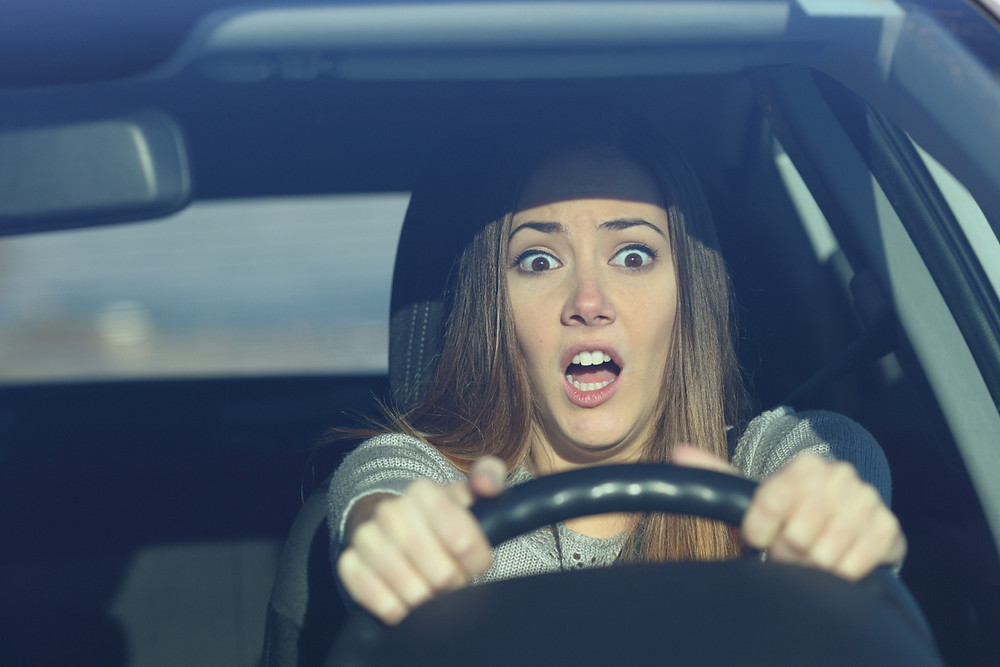 Scared teen driver gripping the steering wheel and gasping