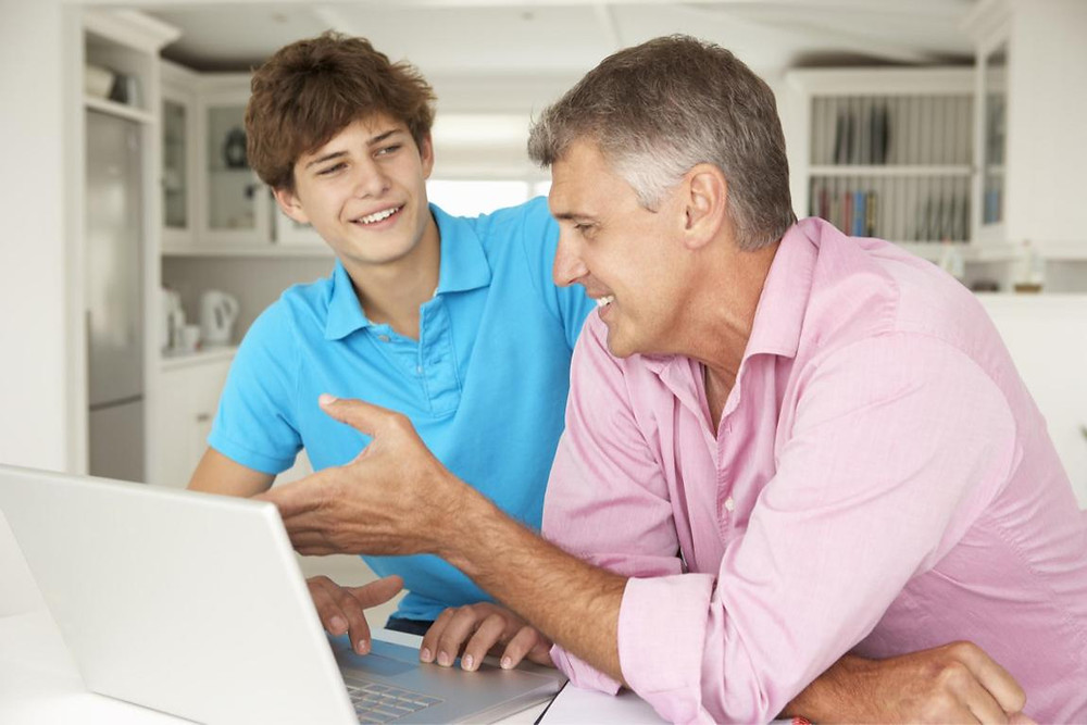 Dad and teen son discussing while looking at computer