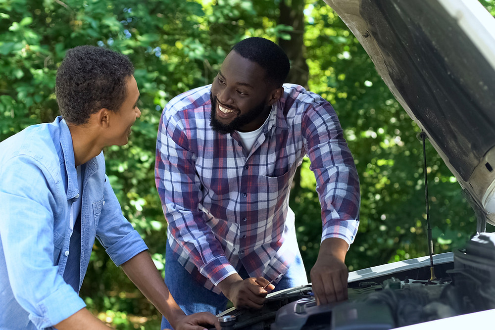 Dad and teen son looking under the hood of car