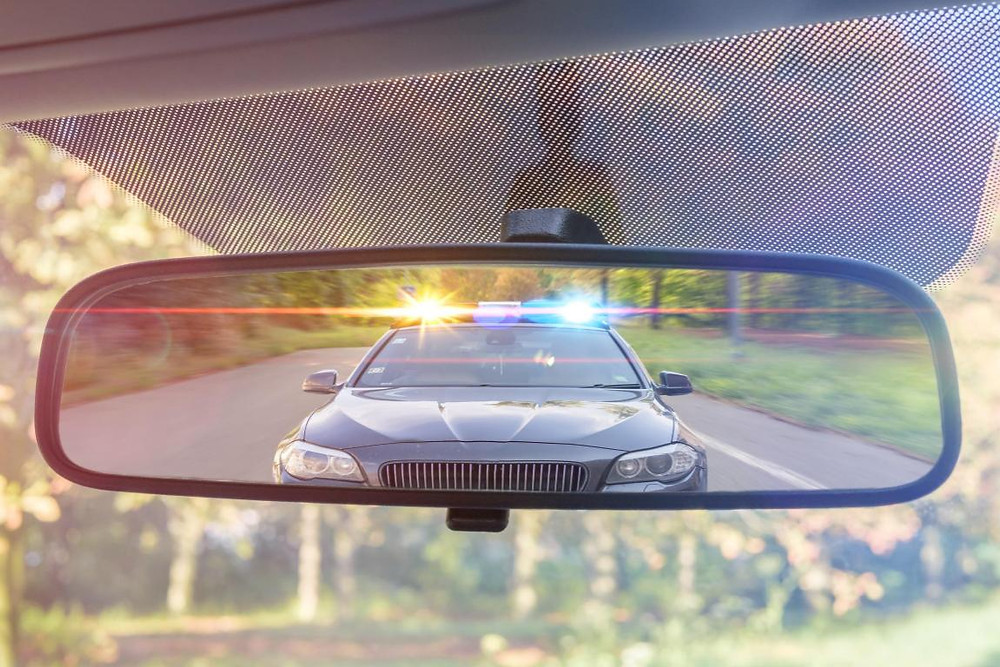 Seeing Police car with lights on in rearview mirror