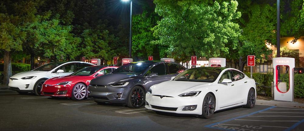 Vários carros Tesla Model 3 abastecendo