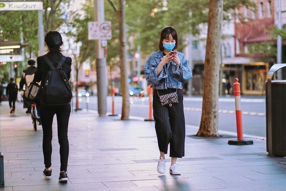 Jovem com máscara e celular na Austrália