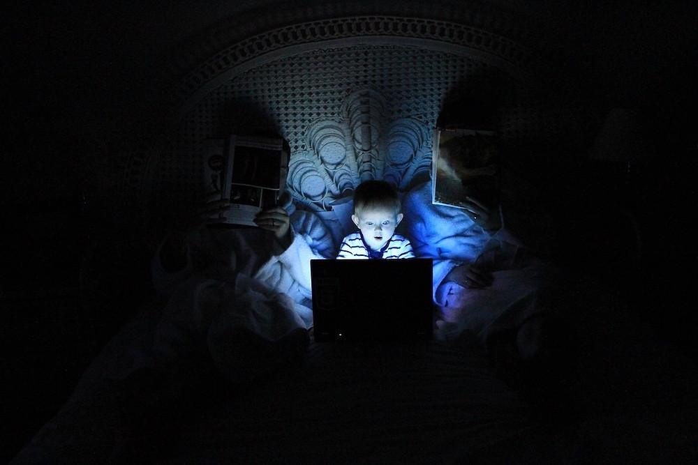 Criança com luz azul no notebook na cama à noite