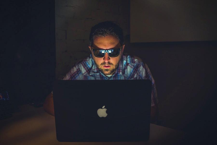 Homem com notebook na escuridão