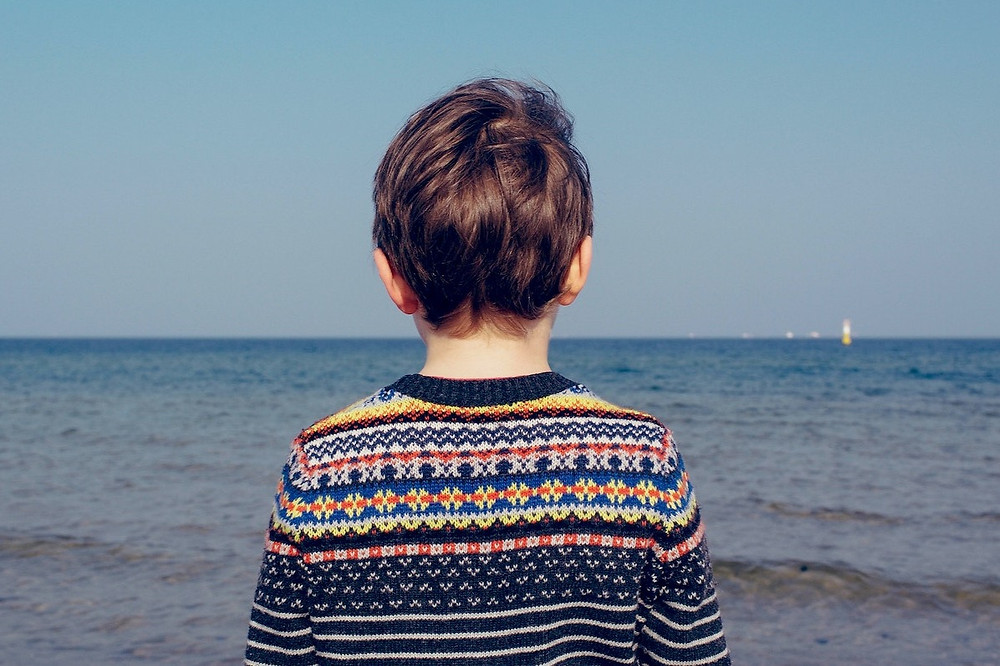 Criança olha o mar