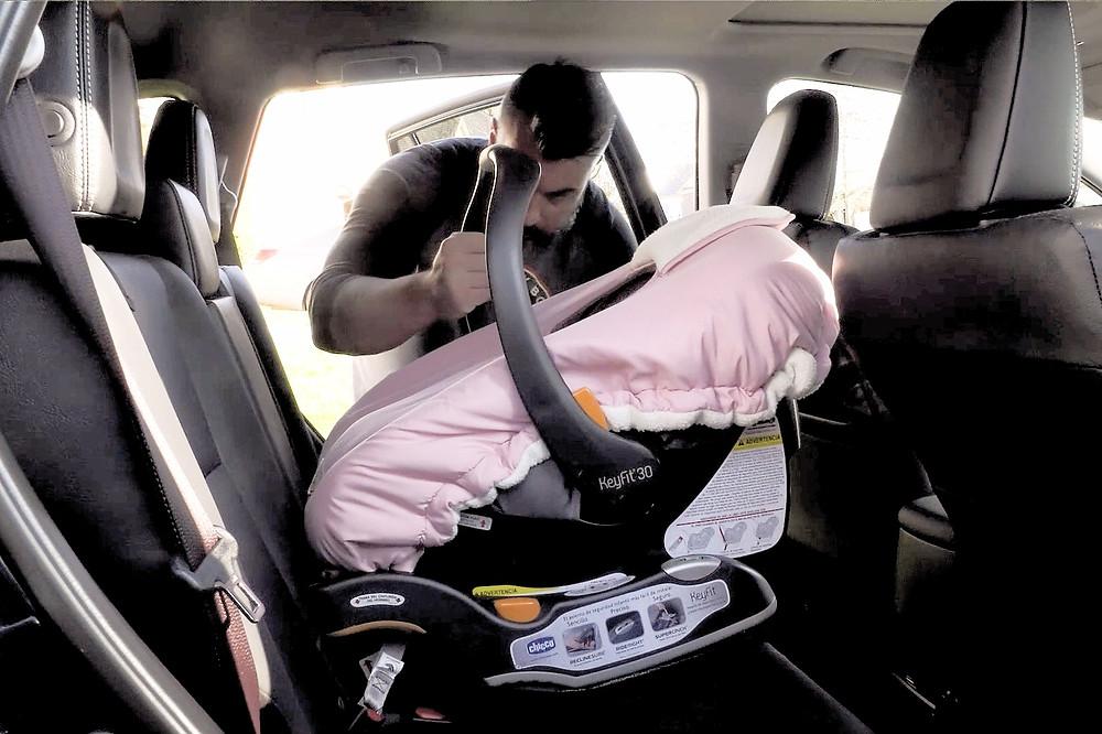 Pai põe cadeirinha com bebê no carro
