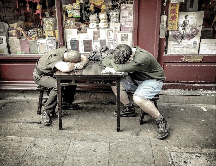 Homens dormem debruçados em mesa
