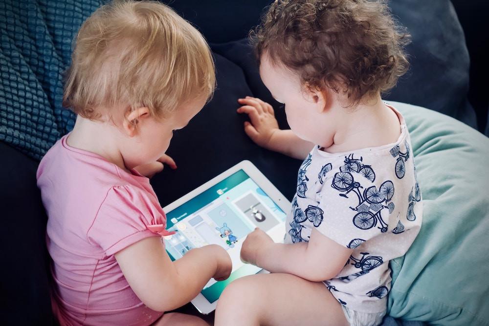Dois bebês brincam com um tablet