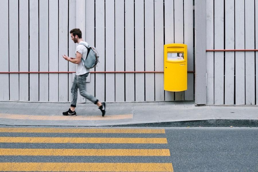 Homem jovem lê no celular em Genebra