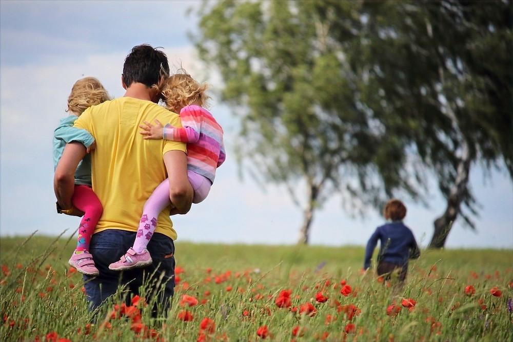 Pai e filhos num campo