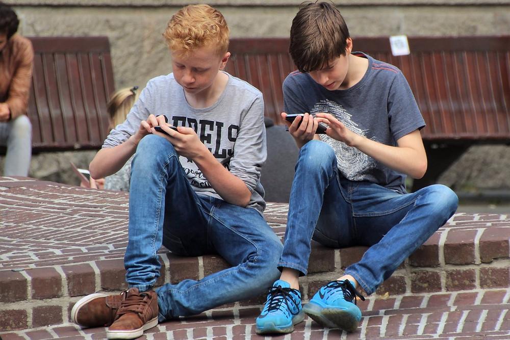 Dois garotos sentados usando celular
