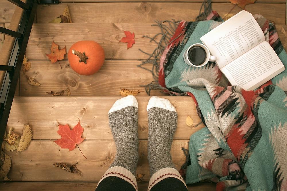 Pés com meia grossa e um livro no inverno