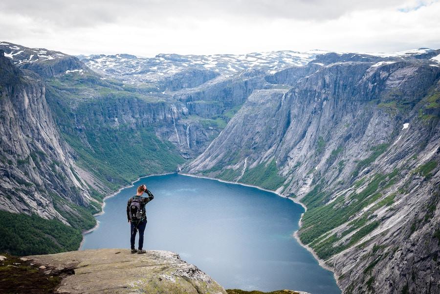 Jovem olha lago entre montanhas
