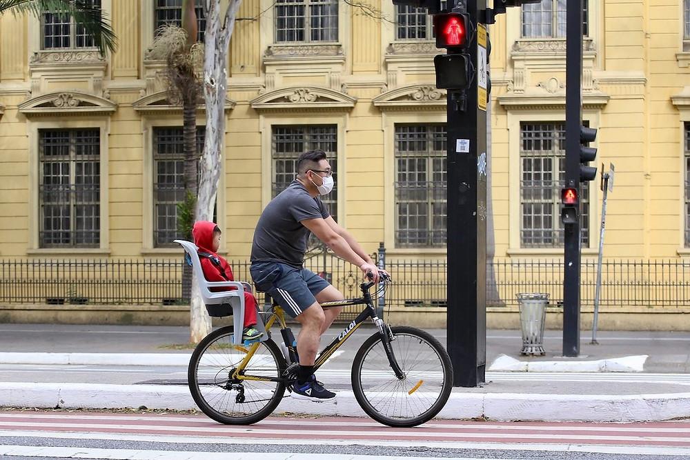 Homem com criança em bicicleta