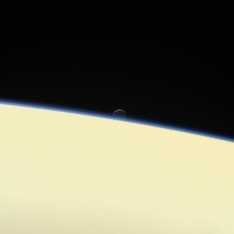 Uma das luas de Saturno, a Encedalus, abaixando atrás do planeta, numa despedida da Cassini