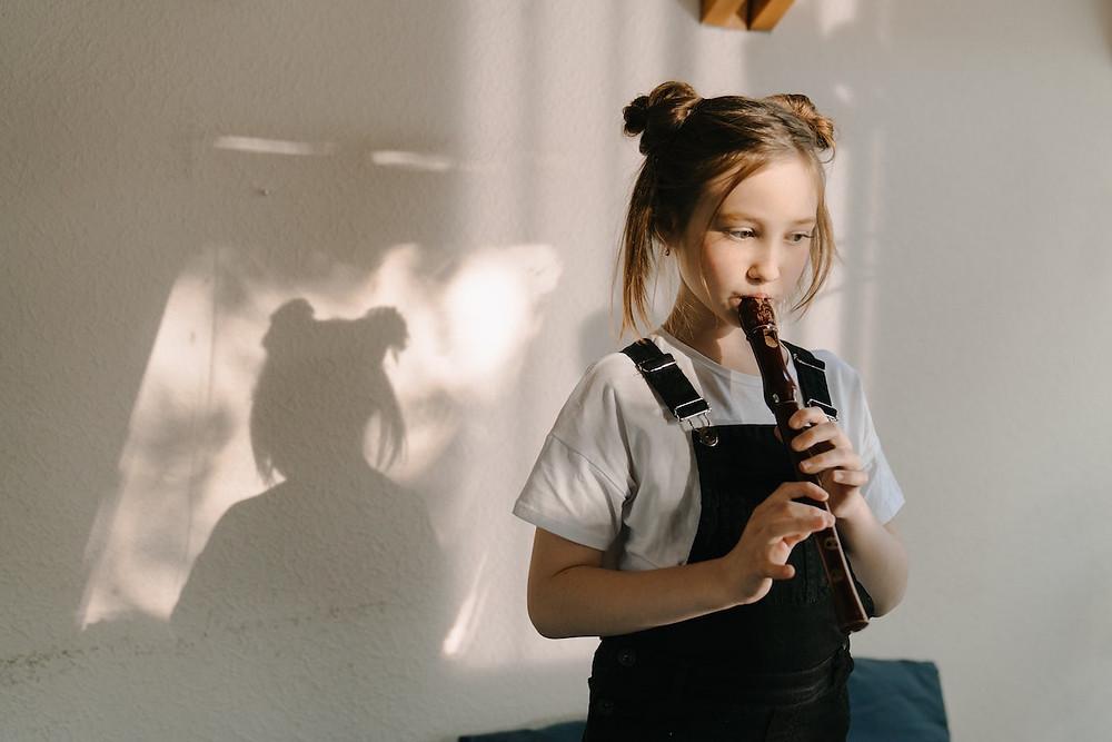 Criança toca flauta