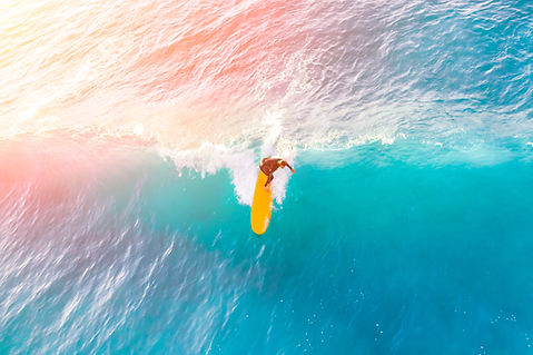 Surfer on a yellow surfboard in the ocea