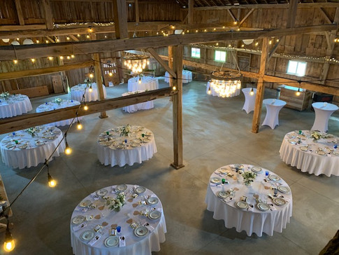 Round table layout for 120 guests.  Dance floor centered in the barn with spacious bar reception social area