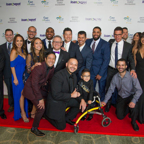 Photo of a young child in a walker and group of adults at UCP-OC's Life Without Limits Gala
