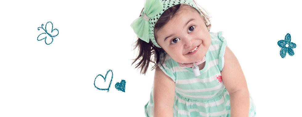 Young toddler girl with special needs smiling at the camera