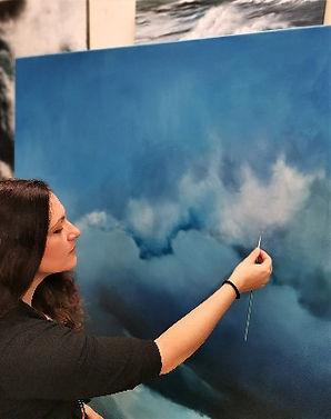 Portrait of ofine artist Marina Syntelis painting a large canvas in progress.