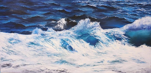 Close-up of a bright, sunlit, white wave in the foreground and blue, vivid sea water in the background.