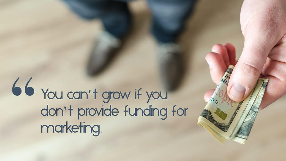 """A wallet showing cash, and the text, """"Want to grow? Build marketing costs into how much you charge."""""""