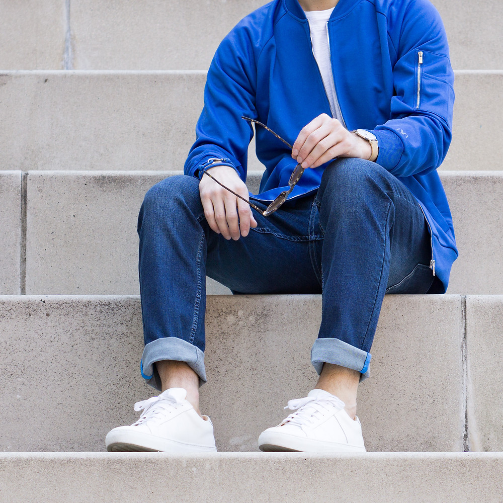 blue denim mugsy jeans rolled cuff with white sneakers and no show socks