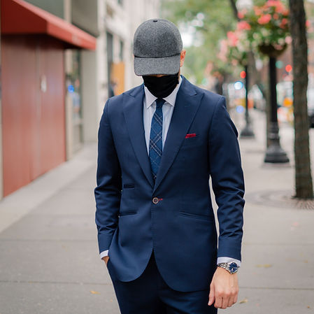 Dapper Professional styling a Vandre luxury hat wearing a face mask and a custom suit with a plaid tie.