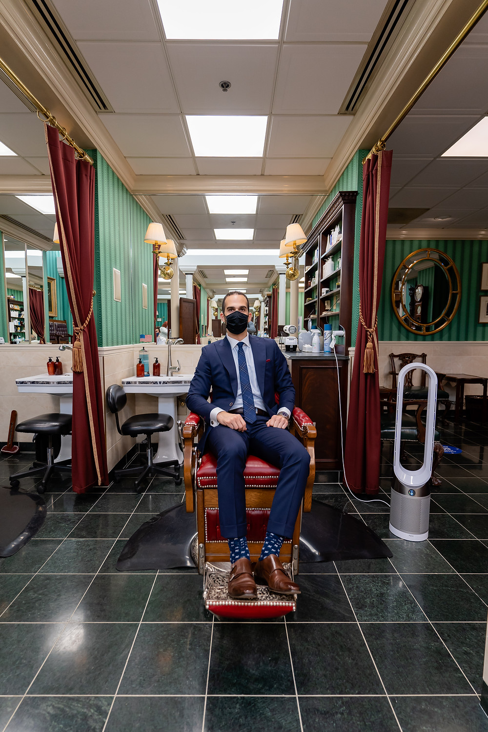 Dapper Professional in a barber chair at Merchant and Rhoades