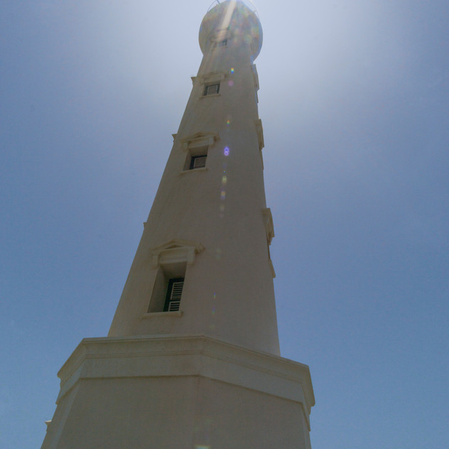 Aruba's California lighthouse with the scorching hot sun behind.