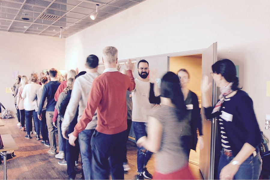 Two rows of people waling towards each other in a leadership and coaching training event