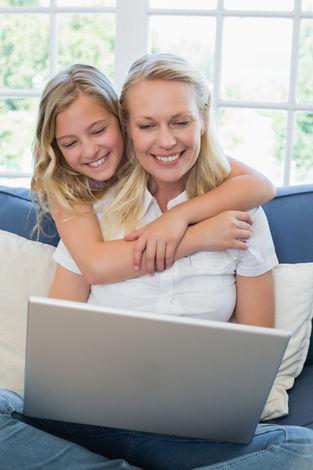 Cute girl embracing mother using laptop