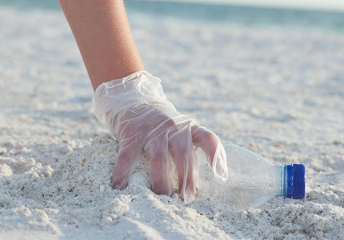 Cleaning Plastic. Hand with glove picking up plastic bottles on beach