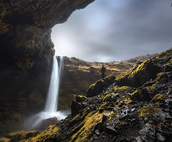 Photographer standing in front of dramatic waterfall in Iceland