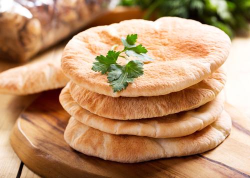 pão sírio pão pita empilhado em tábua de madeira