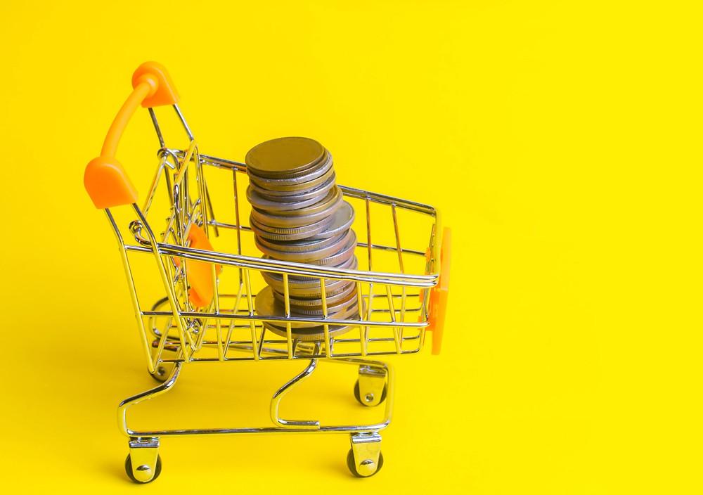 carrinho de supermercado pequeno em um fundo amarelo com moedas dentro