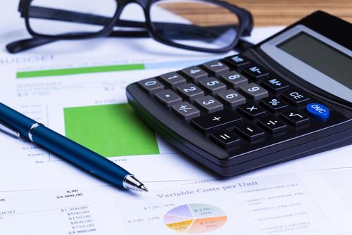 finanças, organize seus gastos. calculadora, caneta e óculos sob planilha