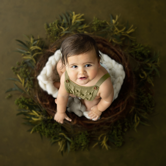 Little child in green sitting in rustic nest